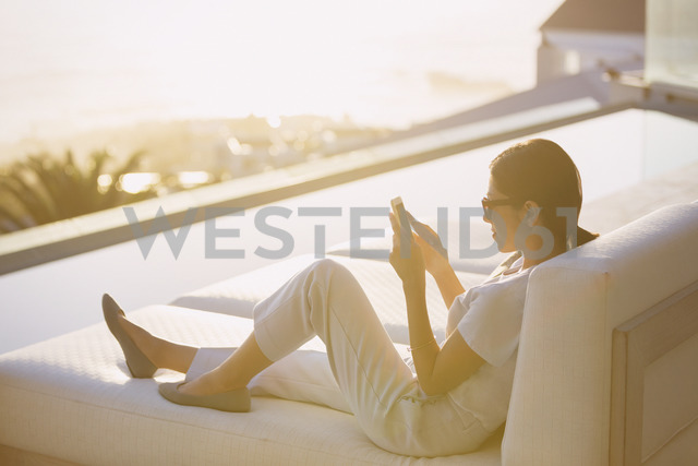 Woman using cell phone on chaise lounge at poolside on luxury patio - HOXF02918