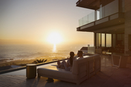 Tranquil sunset ocean view beyond silhouette of couple on luxury home showcase chaise lounge - HOXF02921