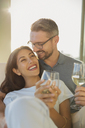 Affectionate couple smiling and drinking white wine - HOXF02924