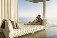 Affectionate couple drinking wine on tufted chaise lounge with ocean view - HOXF02927