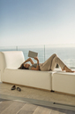 Woman using digital tablet relaxing laying on chaise lounge on luxury balcony with ocean view - HOXF02936