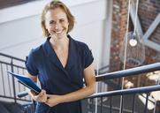 Portrait smiling businesswoman in stairway - HOXF02975