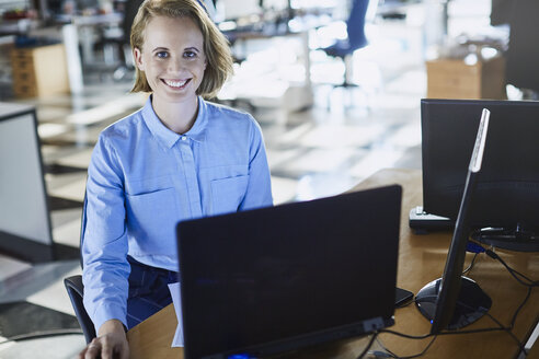 Portrait smiling businesswoman working at laptop in office - HOXF03068