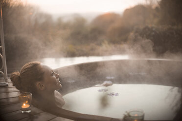 Serene woman soaking in steaming hot tub with autumn tree view - HOXF03089
