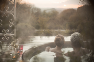 Serene couple in hot tub looking at autumn tree view - HOXF03092