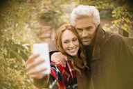 Couple hugging taking selfie with camera phone in garden - HOXF03098