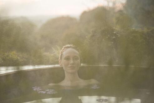 Portrait serene woman soaking in hot tub on autumn patio - HOXF03101