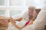 Couple relaxing laying in bed using digital tablet - HOXF03110
