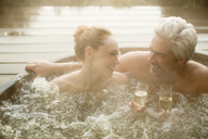 Smiling couple drinking champagne soaking in hot tub on patio - HOXF03116