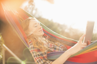 Woman relaxing in sunny hammock using digital tablet - HOXF03122
