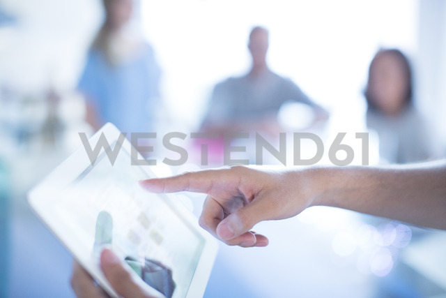 Close up businessman pointing to digital tablet in meeting - HOXF03143