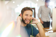 Portrait enthusiastic creative businessman listening to headphones in office - HOXF03152