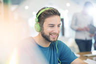 Smiling creative businessman listening to headphones in office - HOXF03164