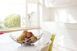 Apples in wire basket on modern kitchen table - HOXF03191