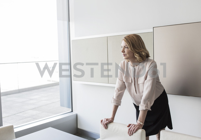 Pensive businesswoman looking out office window - HOXF03200