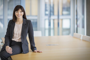 Portrait smiling businesswoman leaning on conference table - HOXF03203