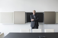 Portrait confident senior businessman in conference room - HOXF03206