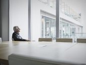 Pensive senior businessman looking out conference room window - HOXF03209