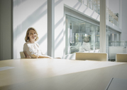 Portrait smiling businesswoman in sunny conference room - HOXF03212