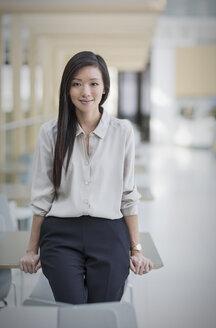 Portrait confident businesswoman leaning on desk - HOXF03218