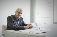 Portrait confident senior businessman working in conference room - HOXF03230