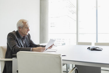 Senior businessman reviewing paperwork in conference room - HOXF03233