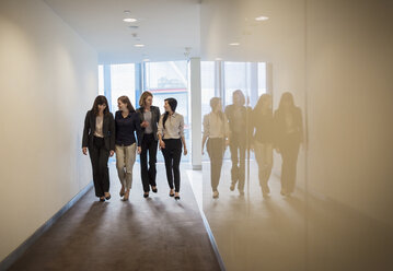 Businesswomen walking in a row in office corridor - HOXF03236