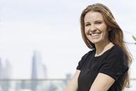 Portrait smiling businesswoman on urban balcony - HOXF03245