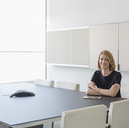 Portrait confident businesswoman with digital tablet in conference room - HOXF03251