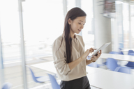 Businesswoman using digital tablet in office - HOXF03257