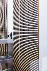 Business people talking on walkway in modern office atrium - HOXF03263