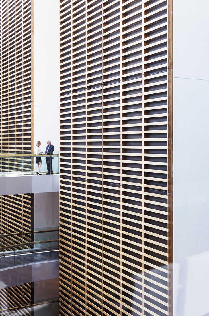 Business people talking on walkway in modern office atrium - HOXF03263 - Martin Barraud/Westend61