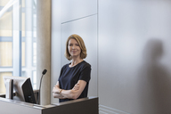 Portrait confident businesswoman at conference room podium - HOXF03266