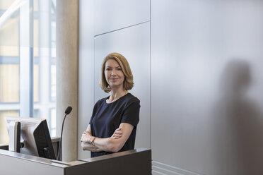 Portrait confident businesswoman at conference room podium - HOXF03266