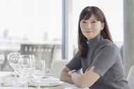 Portrait smiling businesswoman at restaurant table - HOXF03275