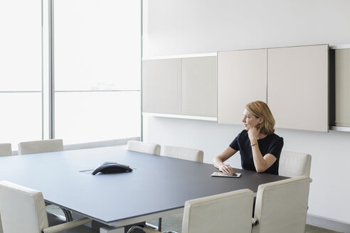 Pensive businesswoman with digital tablet in conference room - HOXF03281