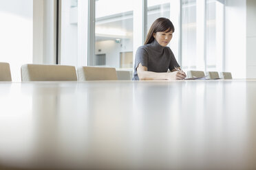 Businesswoman working in conference room - HOXF03290