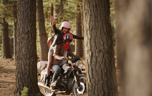 Exuberant young woman riding motorcycle in woods - HOXF03323