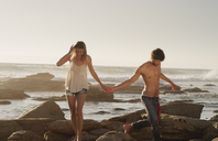 Young couple holding hands and walking on ocean rocks - HOXF03326