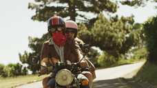 Young couple riding motorcycle on sunny road - HOXF03332