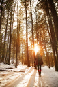 Woman standing amidst trees on snow covered field during sunset - CAVF00008