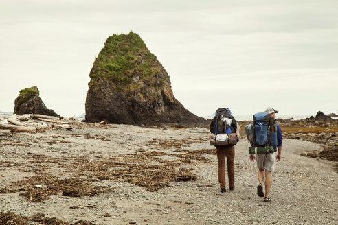 Rear view of hikers walking on dirt road against sky - CAVF00026