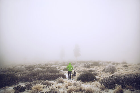 Hiker and dog standing on snow covered field during foggy weather - CAVF00104