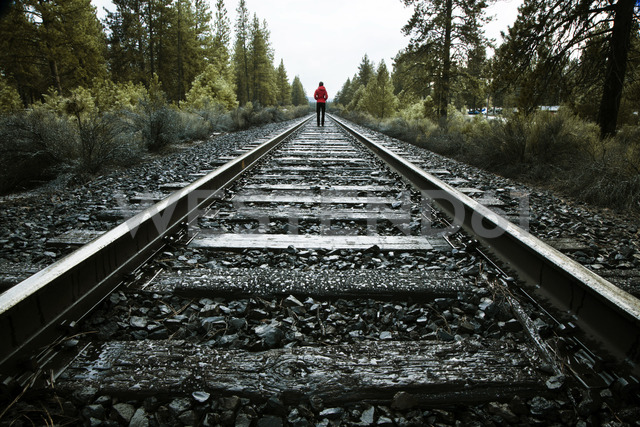 Rear view of woman walking on railroad track at forest - CAVF00137