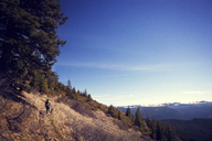 High angle view of hiker walking with dog on mountain against blue sky - CAVF00140