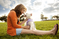 Happy woman playing with dog at grassy field on sunny day - CAVF00182