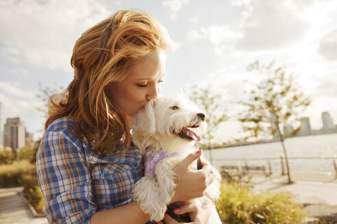 Woman kissing dog against sky on sunny day - CAVF00185