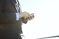 Side view of businessman using smart phone against clear sky - CAVF00203