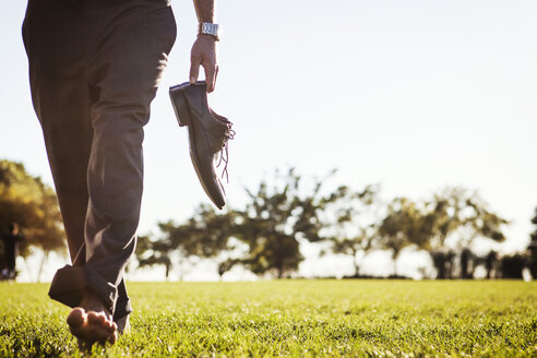 Low section of man holding shoes and walking on grassy field - CAVF00212