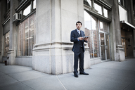 Businessman holding digital tablet and standing against building - CAVF00221